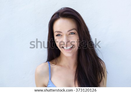 Close up portrait of a cheerful young woman laughing against white wall - stock photo