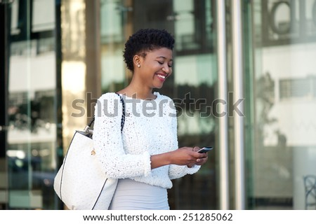 Close up portrait of a cheerful young woman walking with cellphone - stock photo