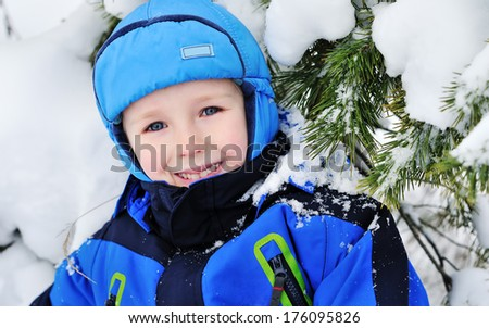 close up portrait of a child lying on the snow in the forest