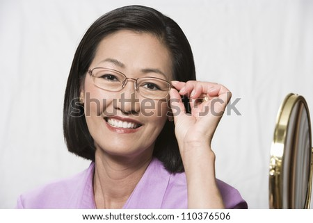Close-up portrait of a Chinese woman trying on glasses