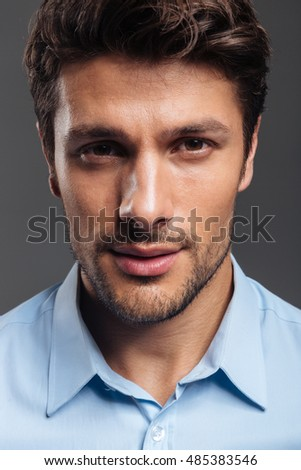 Close up portrait of a confident handsome man in blue shirt isolated on a gray background