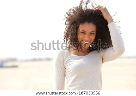 Close up portrait of a confident young woman smiling outdoors - stock photo