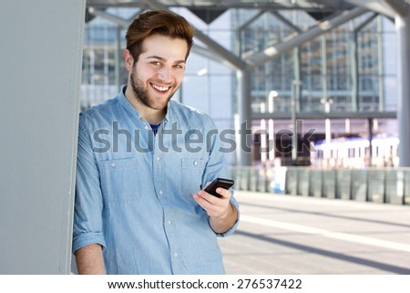 Close up portrait of a cool guy smiling with mobile phone - stock photo
