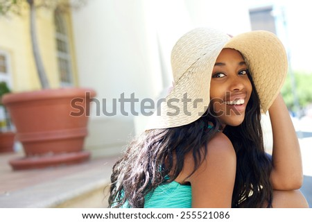 Close up portrait of a cute african american girl laughing with sun hat - stock photo