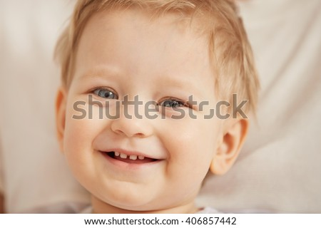 Close up portrait of a cute baby boy, cropped image of an adorable one-and-a-half year old child, smiling and looking at the camera. Cute blue-eyed Caucasian infant with blond hair. Innocent concept  - stock photo