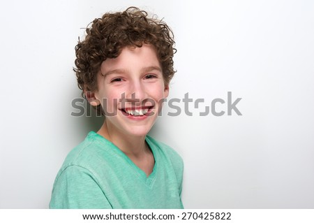 Close up portrait of a cute boy with curly hair smiling on white background - stock photo