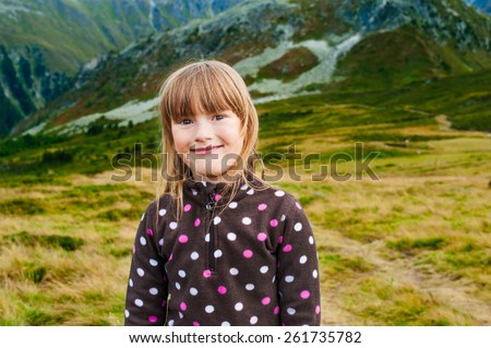 Close up portrait of a cute little girl hiking in mountains, wearing warm fleece jacket - stock photo
