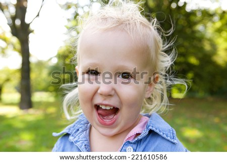 Close up portrait of a cute little girl laughing outdoors - stock photo