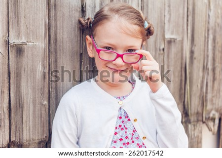 Close up portrait of a cute little girl of 7 years old, wearing pink glasses, standing against wooden background, toned image - stock photo
