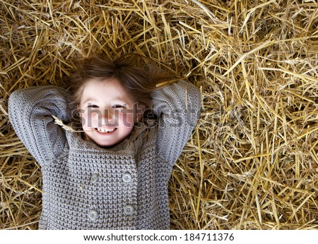 Close up portrait of a cute little girl smiling and lying down on hay. Fun and relaxing - stock photo