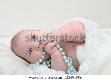 Close-up portrait of a cute 5 month old baby with beads lying on blanket and looking aside. It can be a boy or a girl - stock photo