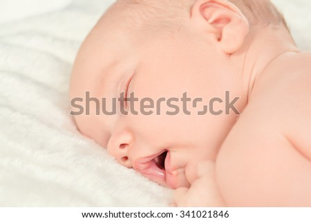 Close-up portrait of a cute newborn baby sleeping peacefully on a soft white blanket.