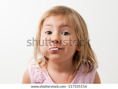 Close up portrait of a cute toddler girl eating a lollypop - stock photo