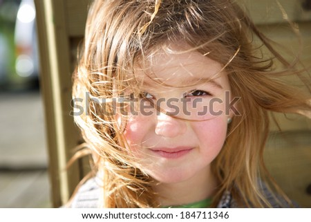 Close up portrait of a cute young girl with hair blowing on face  - stock photo