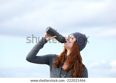 Close up portrait of a fitness woman drinking water from bottle outdoors - stock photo