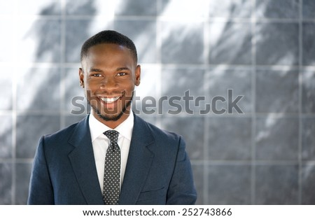Close up portrait of a friendly young businessman smiling - stock photo