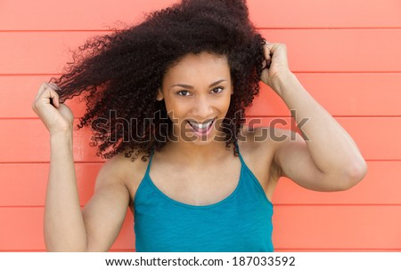 Close up portrait of a friendly young woman smiling outdoors - stock photo