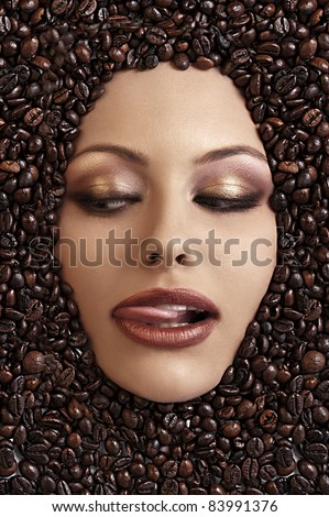 close up portrait of a girl's face immersed in coffee beans sticking her tongue out - stock photo