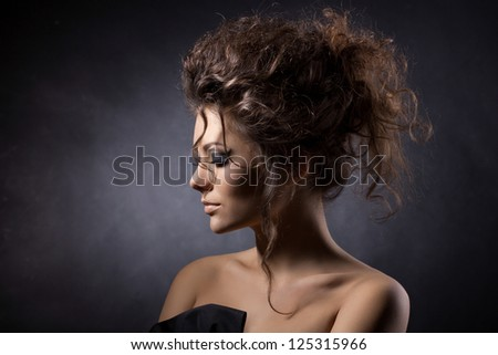close up portrait of a glamorous young woman on dark background - stock photo