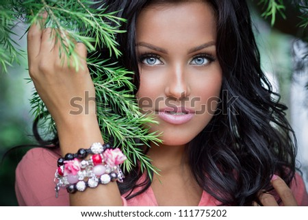 Close up portrait of a gorgeous brunette standing near the tree - stock photo