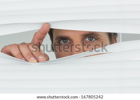 Close-up portrait of a green eyed businessman peeking through blinds in the office - stock photo