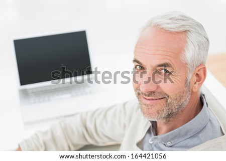 Close-up portrait of a grey haired man with laptop at desk against white background