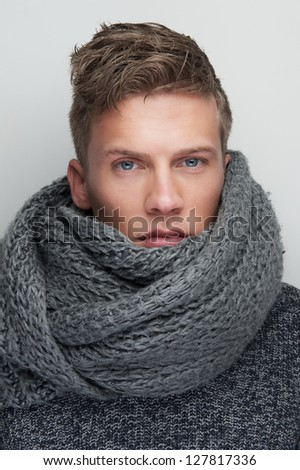 Close up portrait of a handsome man with wool scarf - stock photo