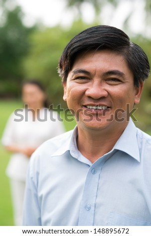 Close-up portrait of a handsome mature man smiling and posing on camera on the foreground - stock photo