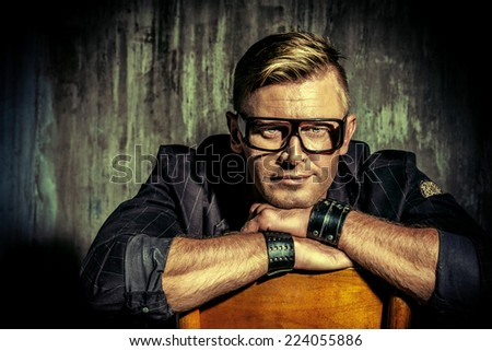 Close-up portrait of a handsome modern man in black suit and spectacles. Men's beauty, fashion. - stock photo