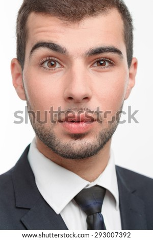Close up portrait of a handsome young bearded man wearing a formal black suit looking at the camera rising his eyebrow, isolated on white background - stock photo