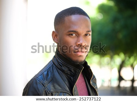Close up portrait of a handsome young black man posing outside - stock photo