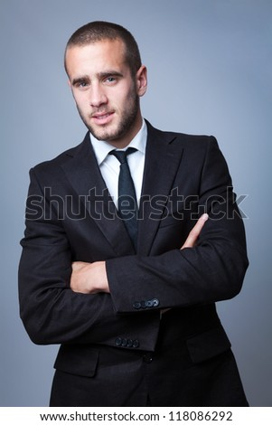 Close-up portrait of a handsome young business man on grey background - stock photo