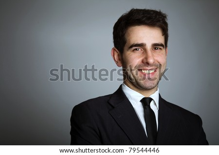 Close-up portrait of a handsome young business man on grey background