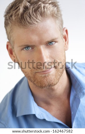Close-up portrait of a handsome young man against white neutral background