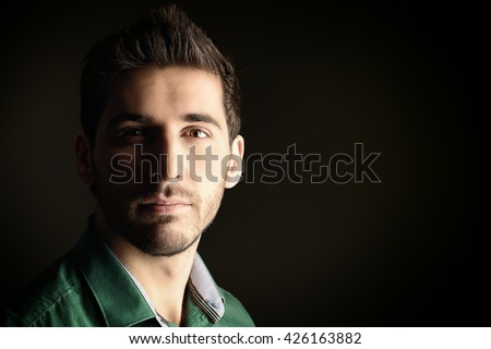 Close-up portrait of a handsome young man looking at camera and slightly smiling. Men's beauty. Studio shot over black background. - stock photo