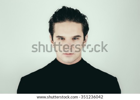 Close up portrait of a handsome young man looking at camera. Goodlooking male face in black dress on white background not isolated. - stock photo