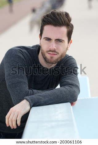 Close up portrait of a handsome young man posing outdoors with serious expression