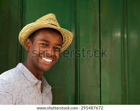 Close up portrait of a handsome young man smiling with hat on green background  - stock photo