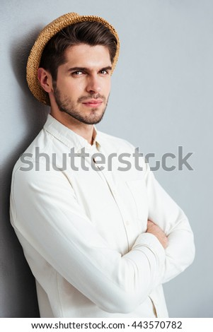 Close-up portrait of a handsome young man standing with arms folded and looking at camera isolated on a gray background - stock photo