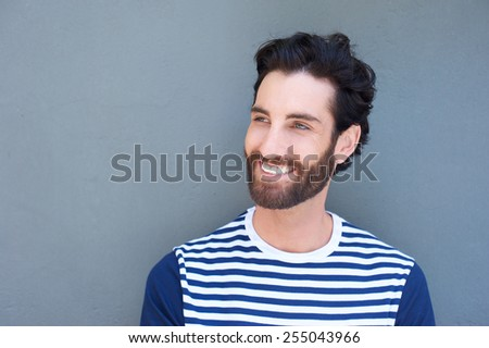 Close up portrait of a handsome young man with beard smiling on gray background - stock photo