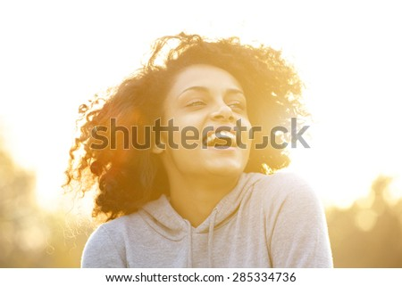 Close up portrait of a happy african american girl laughing outdoors  - stock photo