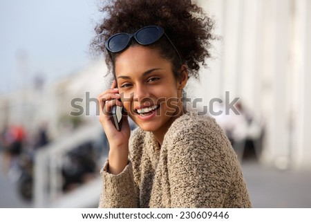 Close up portrait of a happy african american woman calling by cellphone outdoors - stock photo