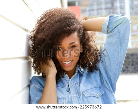Close up portrait of a happy african american woman smiling outdoors with hand in hair - stock photo
