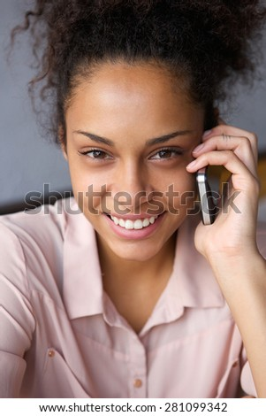 Close up portrait of a happy african american woman using mobile phone - stock photo