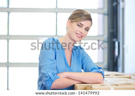 Close up portrait of a happy business woman relaxing by boxes - stock photo