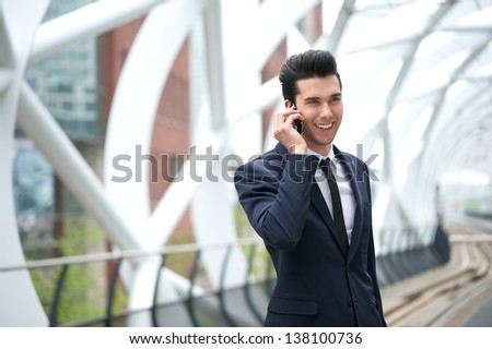 Close up portrait of a happy businessman talking on the phone at subway station - stock photo