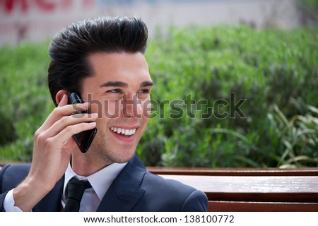 Close up portrait of a happy businessman talking on the phone outside the office - stock photo