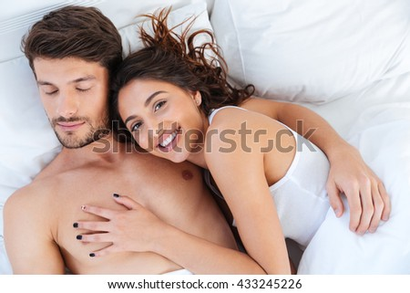 Close-up portrait of a happy couple sleeping and hugging in bed at home - stock photo