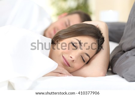 Close up portrait of a happy couple sleeping on a comfortable bed at home or hotel - stock photo