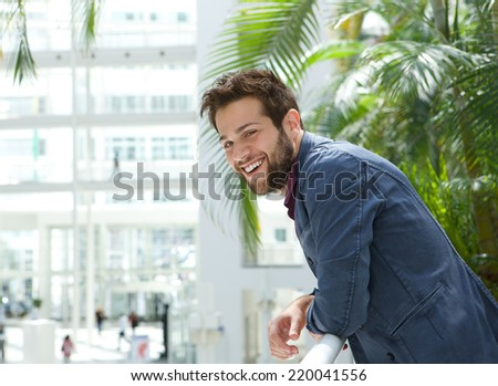 Close up portrait of a happy man leaning inside bright building - stock photo